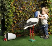 The small child plays with an artificial stork Royalty Free Stock Image