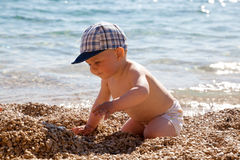 The small child plays on a beach Stock Photo