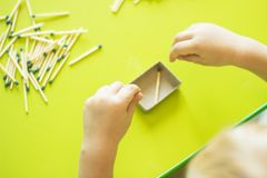 A small child plays with matches, matches matches into boxes, close-ups, fire, lucifer match, hand royalty free stock photography