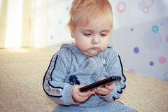 A small child plays with a mobile phone Stock Photography
