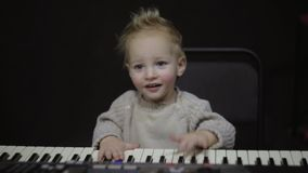 Small child plays the piano. Small boy plays the piano. Cute smiling child tries to play the piano stock video footage