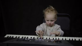 Small child plays the piano. Cute smiling child tries to play the piano stock footage
