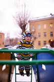 Small child plays at playground in winter Royalty Free Stock Images