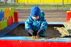 The small child plays in a sandbox. The small child plays in sandbox royalty free stock photo
