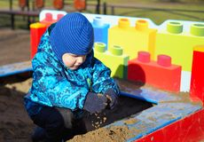 The small child plays in a sandbox Royalty Free Stock Photography