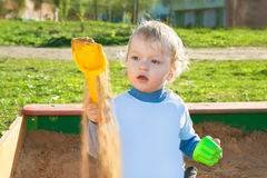 Small child plays in a sandbox Stock Photos