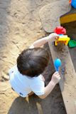 The small child plays in a sandbox with toys Royalty Free Stock Image