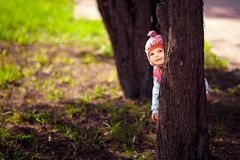 Small child hiding behind a tree. Small child plays Spring Park, hiding behind a tree stock photos