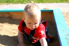 The small child plays to a sandbox Stock Images