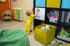 A small child plays with toys in the children`s room pasted Royalty Free Stock Image