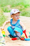 A small child plays with toys on the sand Royalty Free Stock Photography
