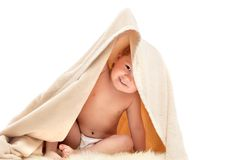 Small child plays under beige towel Royalty Free Stock Photo
