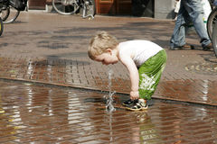 Small child plays with water Stock Images