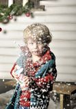 Small child presses a bottle with artificial snow Royalty Free Stock Images
