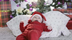 A small child in a red santa suit lying under the Christmas tree and smiles. stock footage