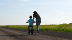 A small child rides a Bicycle with a caring mother who teaches him to ride a Bicycle. Happy family, the concept of an