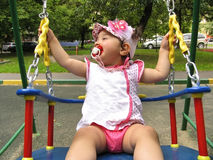 Small child rides on the chain swing Royalty Free Stock Photography