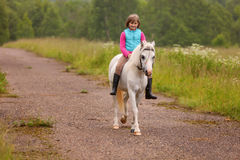 Free Small Child Riding On A White Horse On The Road Outdoors Stock Photography - 57191232