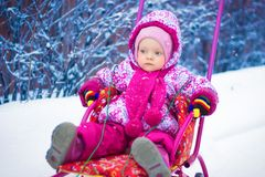 Small child is riding on a sled in the winter Royalty Free Stock Photography