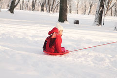 A small child riding on sledge in snow Royalty Free Stock Image