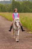 Small child riding on a white horse on the road  Outdoors Royalty Free Stock Image