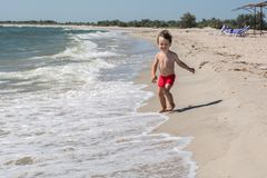 A small child runs along the seashore afraid of wave hair develop in the wind, Royalty Free Stock Photo