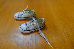 Small child`s canvas shoes on an oak floor. Royalty Free Stock Images