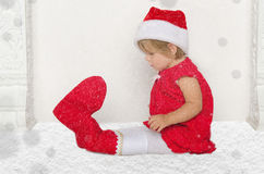 Small child in Santa suit sitting on floor with snow Royalty Free Stock Image