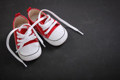 Small child shoes on blackboard. Small sized canvas shoes for kid displayed on blackboard Royalty Free Stock Photo