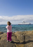 A small child on the shore watching a ship at sea Royalty Free Stock Photo