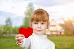 A small child showing a big paper heart. A closeup of a small smiling child showing a big red paper heart at the blurred village house landscape background. The royalty free stock image
