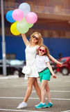 Small child and sister in sunglasses having fun outdoors with lots of colorful balloons. Happy family life. summer holidays stock photography