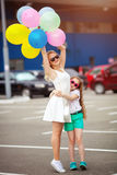 Small child and sister in sunglasses having fun outdoors with lots of colorful balloons. Happy family life. summer holidays happy family life royalty free stock images