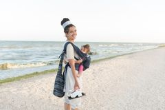 A small child sits in a backpack and walks along with the mother along the seashore. Summer family vacation concept stock image