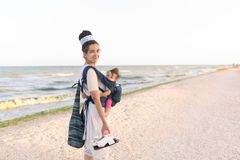 A small child sits in a backpack and walks along with the mother along the seashore. Summer family vacation concept Stock Photo