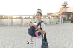 A small child sits in a backpack and walks along with the mother along the seashore. Summer family vacation concept royalty free stock image