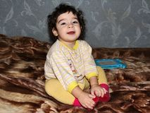Small child sits on blanket, crossing her legs Stock Image