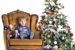 Small child sits in chairs about a Christmas tree Royalty Free Stock Photo