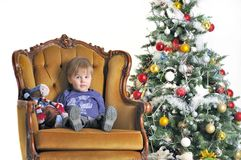 Small child sits in chairs about a Christmas tree Royalty Free Stock Photos