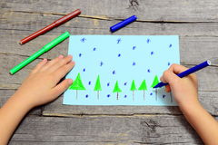 Small child sits and draws Christmas trees and snowflakes on paper. Child holding blue marker in hand and drawing a snowflake Royalty Free Stock Photos
