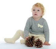 Small child sits on the floor playing with pine Royalty Free Stock Images