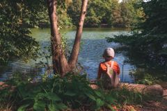 Small child sits in the forest near the pond and enjoys the beautiful nature. royalty free stock photos