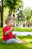 Small child sits on the grass in the Park Stock Image