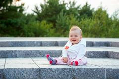 A small child sits on the ground. And laughs royalty free stock photo