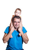 A small child sits at a happy father's shoulders. Portrait royalty free stock photography