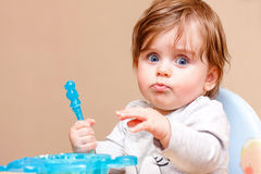 Small child sits at a table and eats. Royalty Free Stock Image