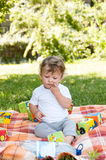 Small child sits among the toys and Royalty Free Stock Photos