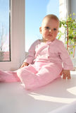 The small child sits on a window sill Royalty Free Stock Image