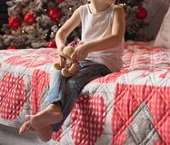 A small child is sitting on a bed with a moose near a New Year tree, in jeans, and a white T-shirt, barefoot.Christmas morning stock photography