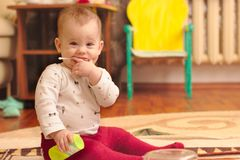 A small child is sitting on the floor in the room and playing with ear sticks. Baby, kid, kids, home, happy, young, toy, white, cute, people, fun, laughing stock photo